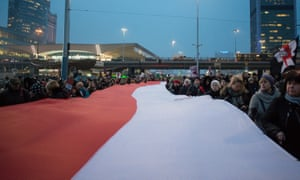 People in Warsaw carry the Polish flag during a protest against plans to further restrict abortion laws in Poland