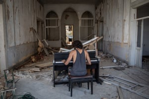 Artist and musician Raymond Essayan plays a piano in a destroyed building following the port explosion in Beirut, Lebanon