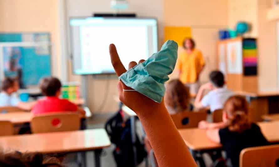 A facemask is seen on the hand of a student raising his arm during class.