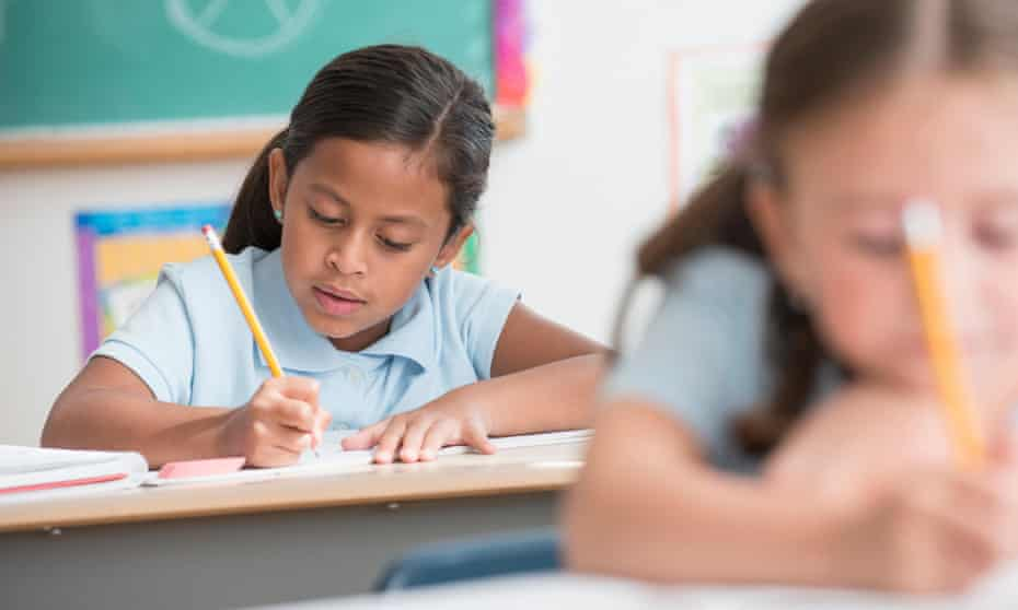 Primary school students writing at desks in classroom