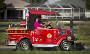 A couple drive a golf cart converted to look like a fire truck in The Villages retirement community.