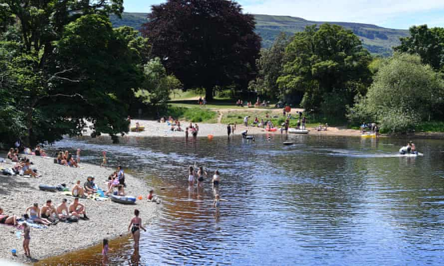 People relax on the banks and paddle in the River Wharfe in Ilkley.