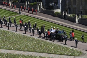 Land Rover with ceremonial guards following on foot