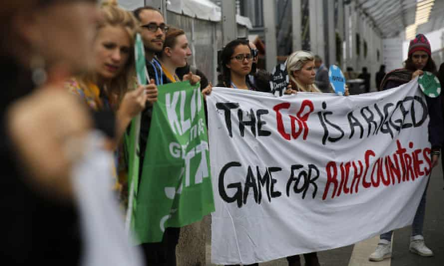 Protesters outside the COP 21 climate talks in Paris holding a sign claiming the process is rigged in favour of rich countries. A divide between the demands of developing and developed nations is emerging over emissions reporting and checking rules.