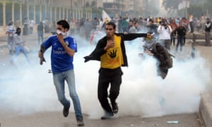 Supporters of Mohamed Morsi run from tear gas during clashes with riot police close to Rabaa al-Adawiya square in November 2013.