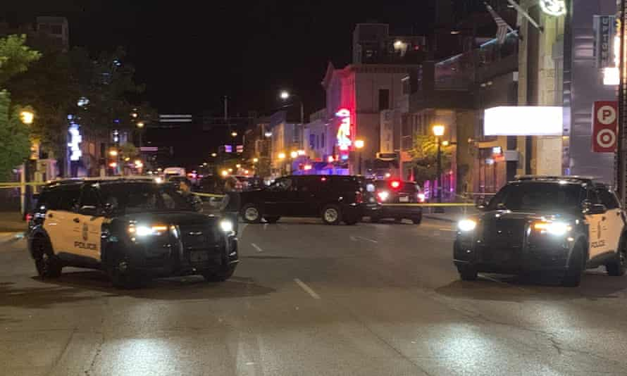 Police vehicles block a street in Minneapolis after a woman was killed and three people injured.