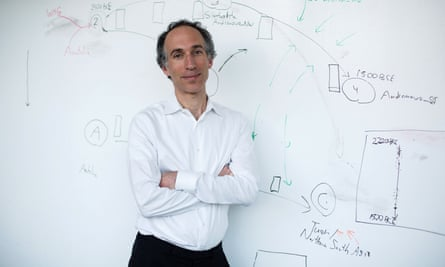 david reich poses for a photo in front of a whiteboard