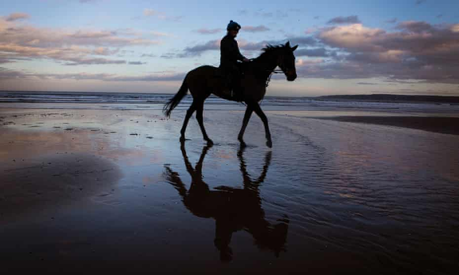 A horse and rider exercise as the sun sets on the beach at Filey.