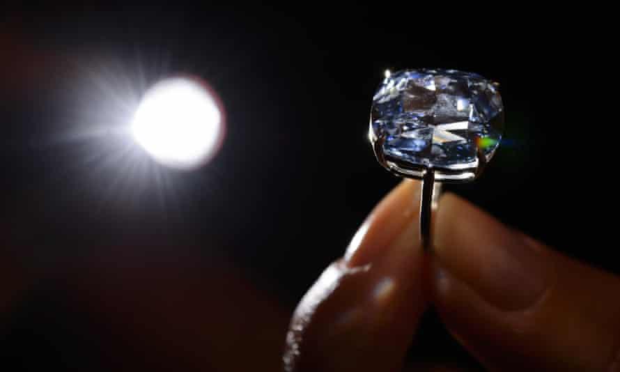 A 12.03-carat blue diamond is held up to view at Sotheby's auction house in Geneva.