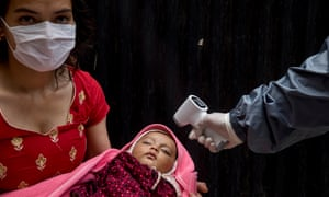 A health worker checks the temperature of a child during a national vaccination campaign in Kathmandu, Nepal.