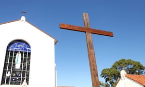 A large wooden cross is seen outside the closed Our Lady of Lourdes Catholic Church