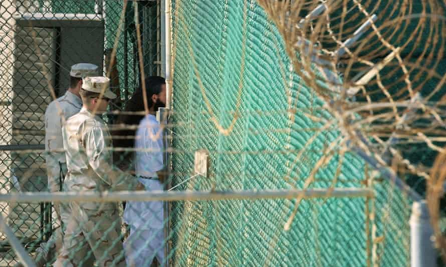 Guards moving a detainee to an undefined facility inside Camp Delta in the Detention Center at Guantánamo Bay, Cuba.
