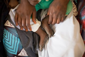 A CDD sits with a child during a training session at Kaduna health centre
