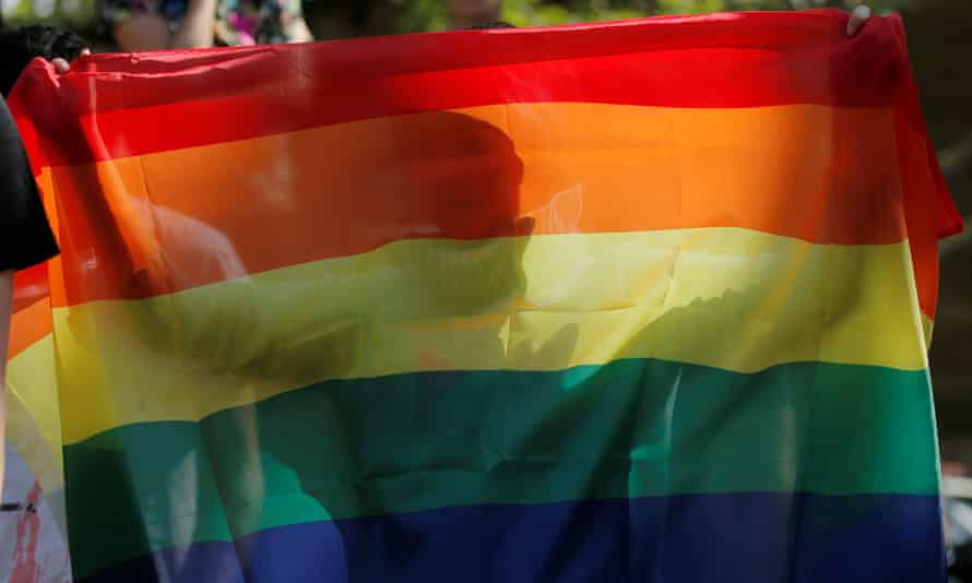 A person is pictured through a rainbow flag