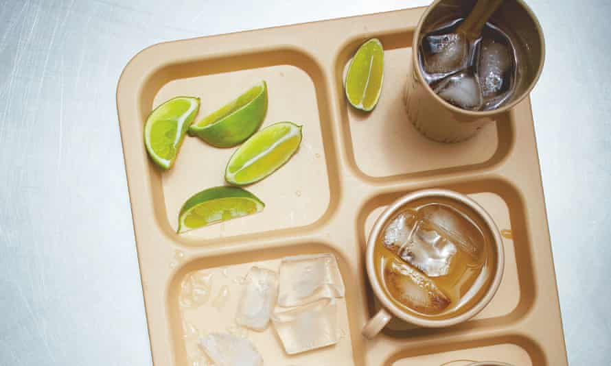 A compartmentalised tray with plastic beakers of dark drink, slices of lime and ice cubes