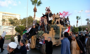 Supporters of Libyan National Army in Benghazi celebrate on top of a Turkish military armoured vehicle, which the LNA said it confiscated during clashes in Tripoli.