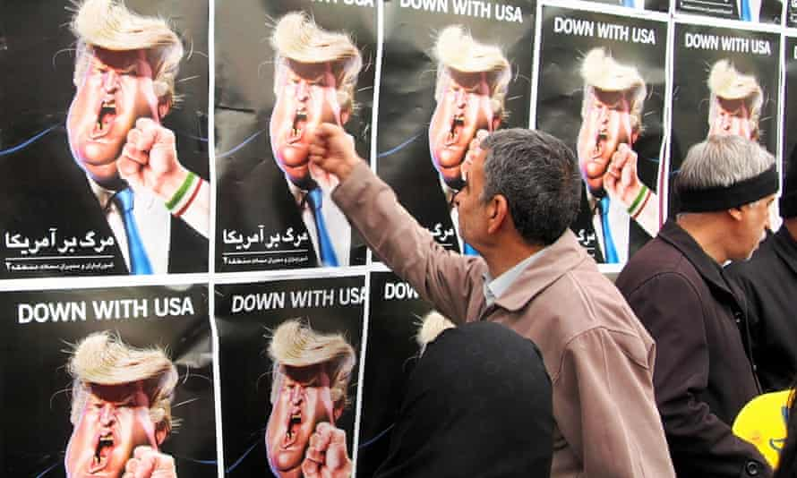 A man holds his fist to a poster depicting Donald Trump in Tehran