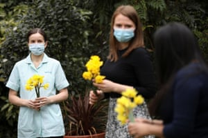 A nurse and two staff members hold daffodils during the day of reflection to mark the anniversary of Britain's first coronavirus lockdown at the Marie Curie hospice in Hampstead