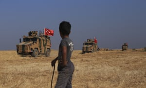A Syrian boy watches Turkish forces on patrol close to the border between the two countries.
