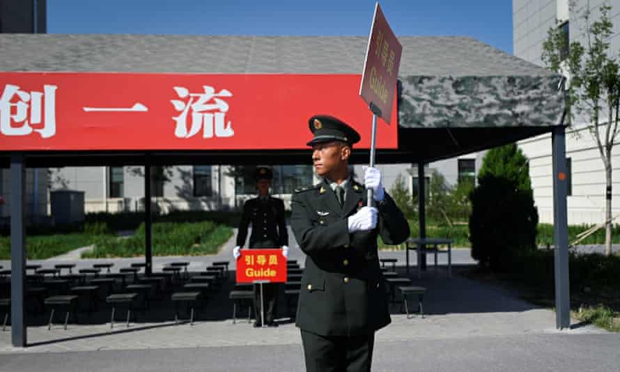 A Chinese soldier holds a signboard to guide journalists during a tour arranged for the media by the press centre in charge of celebrating the 70th anniversary of the country's founding