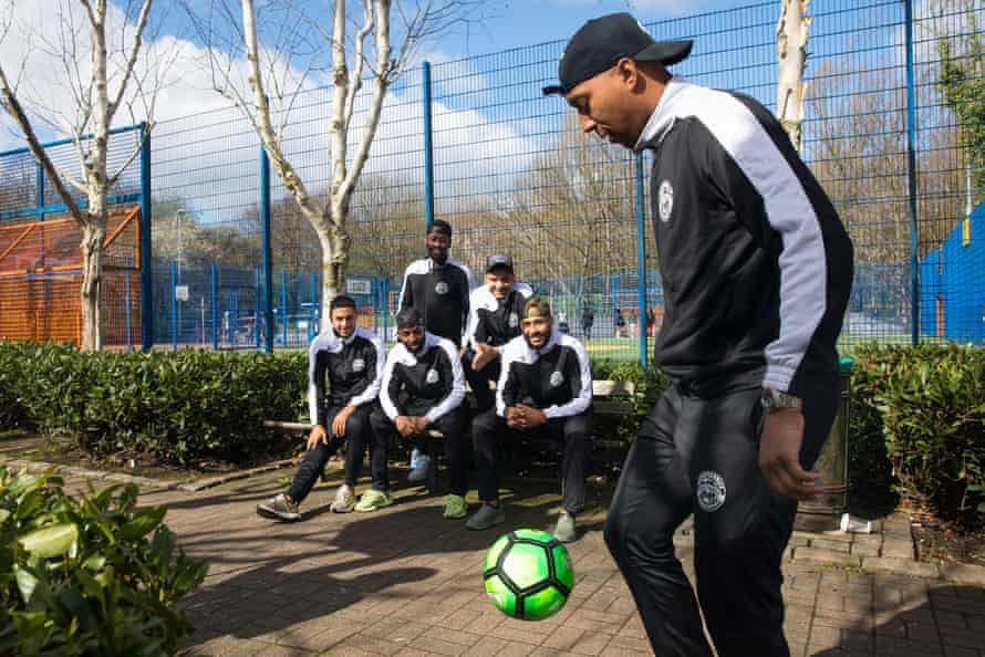 Adrian Clifton juggles a football as his teammates look on.