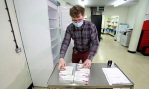 Assistant technical officer Lukasz Najdrowski unpacks doses of the Oxford/AstraZeneca Covid-19 vaccine at the Princess Royal hospital in West Sussex.