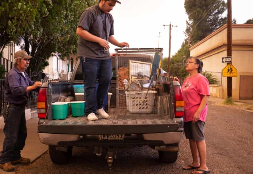 Ralph García, izquierda, Josiah Arvizu y Patsy Arvizu cargan su camión el lunes mientras evacuaban del incendio del Telegraph en Miami, Arizona.