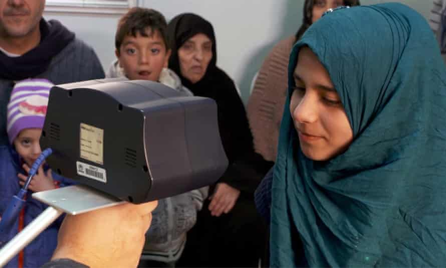 a syrian girl having her iris scanned at a refugee camp in jordan