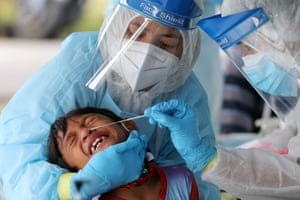 Klang, Malaysia. Medical workers collect a swab sample from a boy to be tested for coronavirus