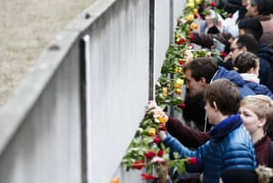 People lay flowers to remains of the Berlin Wall during a commemoration ceremony to mark the 30th anniversary of its fall