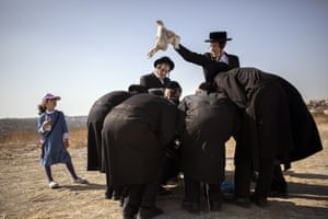 An ultra-orthodox Jewish man swings a chicken above his friends as part of the Kaparot ritual in Beit Shemesh, performed before the day of atonement, Yom Kippur.
