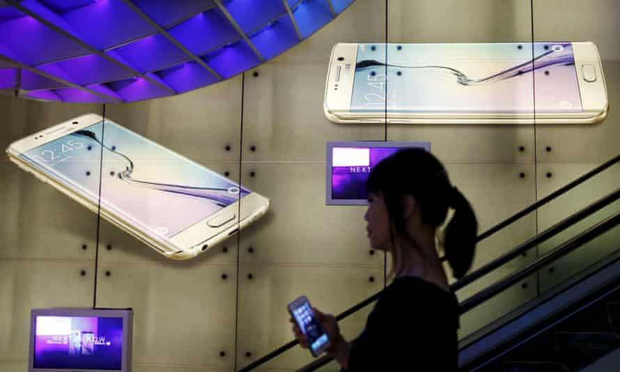 Chinese woman walking past a Samsung advert