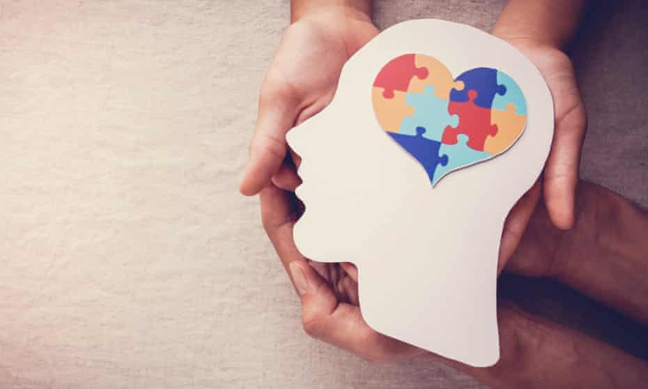Two people's hands holding cut-out of head in profile with heart-shaped jigsaw