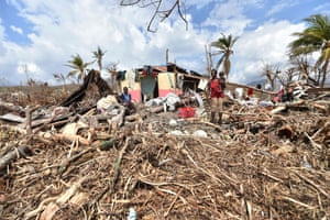 People stand next to their destroyed house in Les Cayes