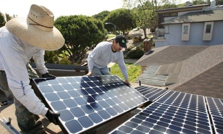 Workers install solar panels on a residential rooftop in Santa Monica, California.