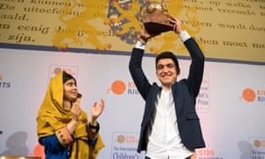 Mohamad Al Jounde holds up the International Children's Peace Prize, given to him by Malala Yousafzai (left).