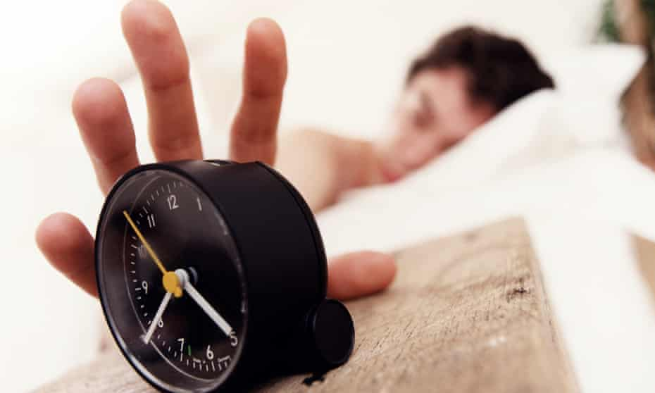 Young man in bed reaching for alarm clock