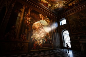 London, UK. A gallery assistant looks at a fresco during the reopening of The Painted Hall, in the Old Royal Navy College