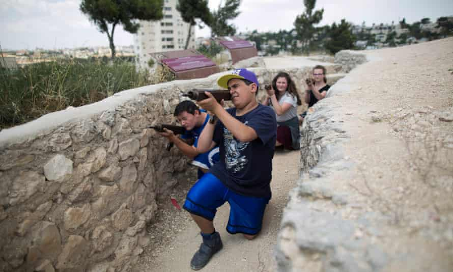 Israeli youths holding mock guns relive the battle for Jerusalem during the six day war in 1967
