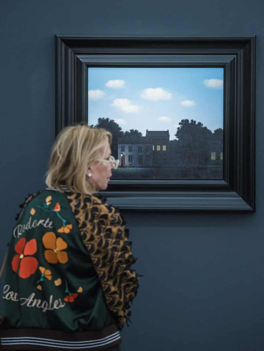 A woman considers L'Empire des Lumieres, 1949, by Magritte at Frieze Masters.