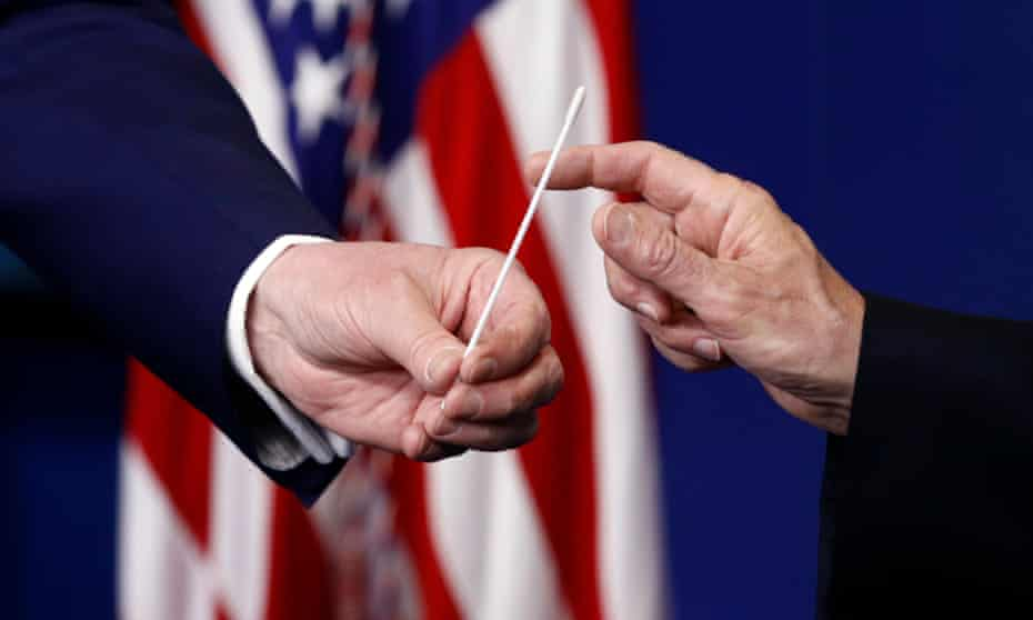 Donald Trump, left, hands a swab that could be used in coronavirus testing to Mike Pence during a taskforce briefing in Washington DC, on 19 April.