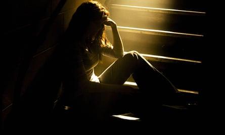 Teenage girl in shadows on stairs