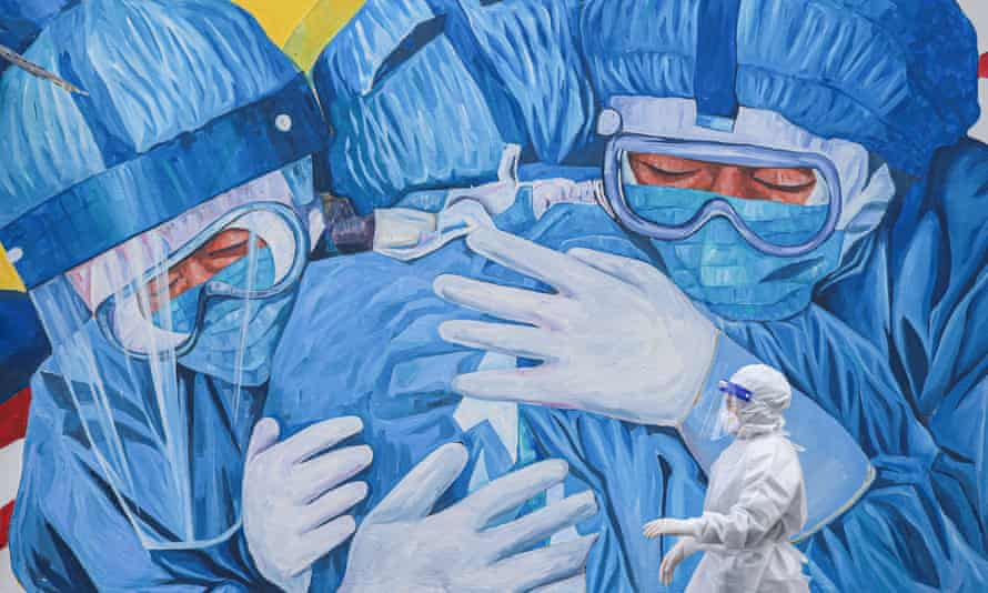 A health worker wearing PPE walks past a mural showing medical staff outside Clinic Ajwa in Shah Alam, Malaysia.
