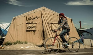 "A migrant rides his bicycle inside the ""Jungle"" camp for migrants and refugees in Calais on June 24, 2016"