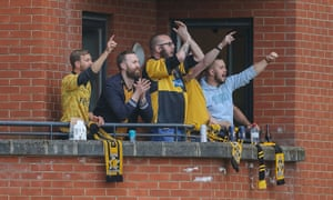 Cambridge fans watch their team's 4-2 win over Leyton Orient from a nearby apartment.