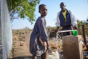Mafoukana Kajoube and his daughter Ajiko Zuhari, 8, from Uganda fetch water
