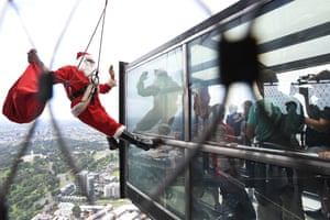 Melbourne, Australia. A stuntman dressed as Santa Claus greets visitors to the Eureka Skydeck observation point, on the 88th floor of the Eureka Tower