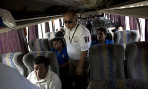 An immigration official checks a bus for Central American migrants at a roadblock north of Arriaga, Chiapas state, Mexico.