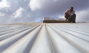 A solar panel technician carrying out maintenance work on a corrugated roof, Miono region, Tanzania.