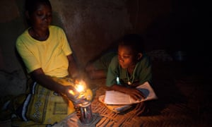 A mother lights a small lamp for her child to study in the central Ugandan town of Masaka